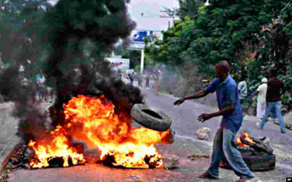 A Haitian throws a tire into fire during a protest following presidential elections in Port-au-Prince December 8, 2010. Protests and sporadic gunfire erupted in Haiti's capital late on Tuesday after electoral authorities announced the country's inconclusi
