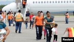 Các phụ nữ và trẻ em đi trong sân bay ở San Pedro Sula sau khi bị trục xuất khỏi Mỹ, 14/7/14