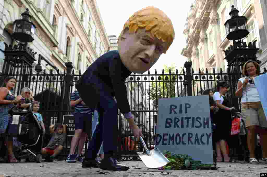 "A demonstrator wearing a mask depicting Britain's Prime Minister Boris Johnson stands beside a mock gravestone inscribed with the words ""RIP British Democracy"" outside the gates to Downing Street in central London."