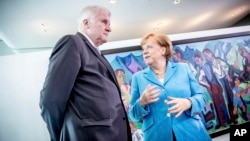 German Chancellor Angela Merkel, right, talks to Interior Minister Horst Seehofer, left, prior to the weekly cabinet meeting at the chancellery in Berlin, June 13, 2018.
