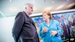 FILE - German Chancellor Angela Merkel, right, talks to Interior Minister Horst Seehofer, left, prior to the weekly cabinet meeting at the chancellery in Berlin, June 13, 2018.