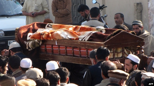Local residents carry the coffin of a bomb blast victim during a funeral in Mingora, Pakistan, January 11, 2013.