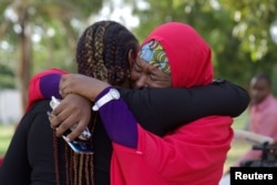 FILE - Members of the #BringBackOurGirls (#BBOG) campaign embrace each other at a sit-out in Abuja, Nigeria, May 18, 2016.