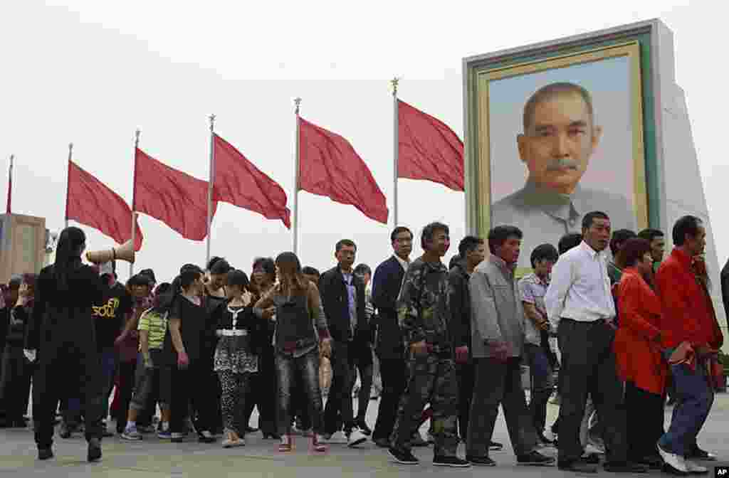 Tens of thousands of visitors flock to Tiananmen Square area to enjoy May Day, a public holiday. People line up in front of a portrait of Sun Yat-sen, to view the embalmed body of the late Chinese leader Mao Zedong at his mausoleum in Beijing, China, Ma