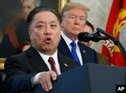 FILE - Broadcom CEO Hock Tan speaks while U.S. President Donald Trump listens during an event at the White House in Washington, Nov. 2, 2017.