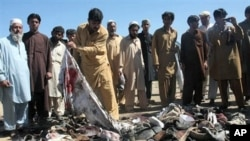 Pakistani villagers search for the belongings of their family members after a blast in Matani near Peshawar, Pakistan, March 9, 2011
