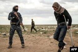 Muškarac, za kojeg se sumnja da je borac Islamske države, prolazi pored člana Sirijske demokratske snage (SDF) i ide na pretres prije nego napusti posljednji uporište Islamske države, Baghouz, Sirija, 27. februar 2019.