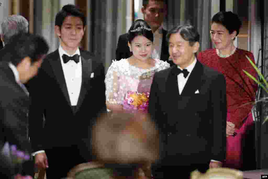 Japan's former princess Ayako Moriya (C) and her husband Kei Moriya (2nd L) arrive at their wedding banquet in Tokyo, with Crown Prince Naruhito (2nd R) and Crown Princess Masako (R) as Prime Minister Shinzo Abe bows.
