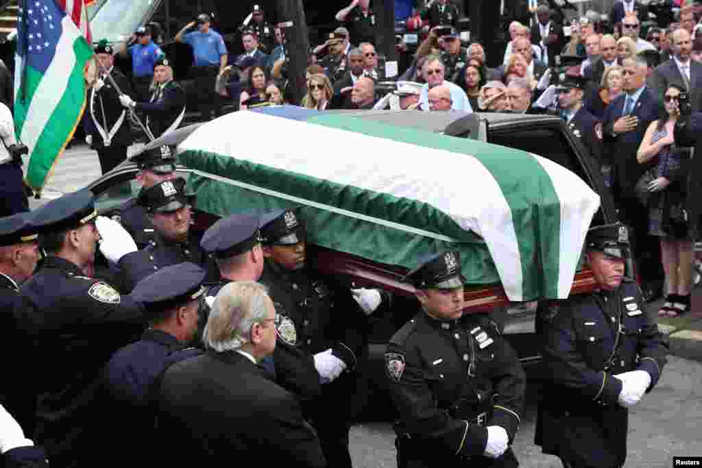 "The casket of Luis Alvarez, a former New York City police detective who got cancer after working at the World Trade Center's ""Ground Zero,"" is carried into a religious center for his funeral in New York City."