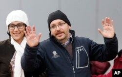 U.S. journalist Jason Rezaian gestures next to his wife Yeganeh Salehi as he poses for media people in front of Landstuhl Regional Medical Center in Landstuhl, Germany, Wednesday, Jan. 20, 2016. Rezaian was released from an Iranian prison last Saturday.