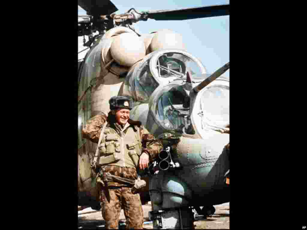 A Soviet soldier puts his arm on the tubes of a MI 24 helicopter's machine gun, at the Soviet military airport in Kabul, Afghanistan, 8 February 1989. Some Soviet troops still remain at Kabul Airport, their mission, apparently, to guard it until the Sovie
