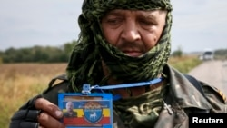 FILE - A pro-Russian separatist shows his ID card to Ukrainian journalists at a checkpoint near the town of Slavyanoserbsk, Luhansk region, eastern Ukraine, Sept. 10, 2014. Some in Ukraine see journalists operating in rebel-held areas as enemy collaborators.