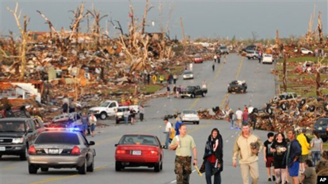Residents of Joplin, Mo, walk west on 26th Street near Maiden Lane after a tornado hit the southwest Missouri city on Sunday evening, May 22, 2011. The tornado tore a path a mile wide and four miles long destroying homes and businesses. (AP Photo/Mike Gul