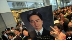 A Thai Democrat party supporter holds a poster of Thai Prime Minister and leader of the party, Abhisit Vejjajiva, during a campaign rally in Bangkok, June 23, 2011