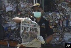Petugas bea cukai memperlihatkan halaman depan sebuah surat kabar asing di antara tumpukan sampah dalam kontainer di Tanjung Perak, Surabaya, 9 Juli 2019.