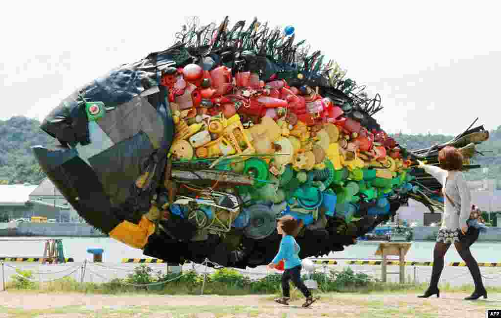 A large sea bream object, made from colorful debris found drifting at sea, such as plastic tanks, toys and wires, and created by Japanese art group Yodogawa Tecnique, is displayed at the Setouchi Triennale art event at the port of Uno, Okayama prefecture, Japan.