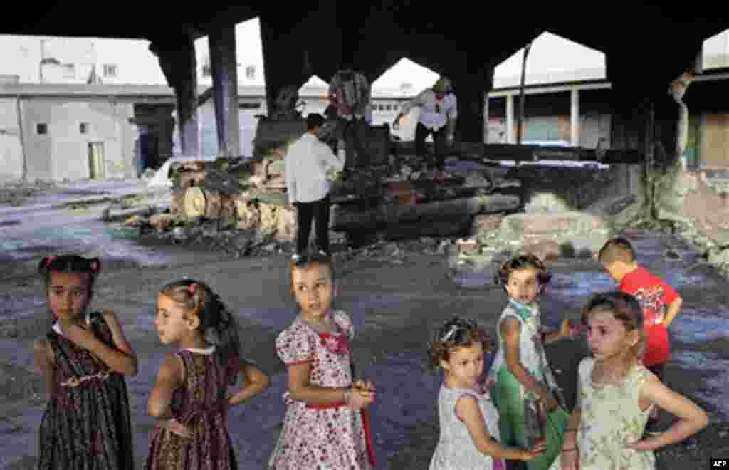 Children seen in front of a destroyed tank at the vegetable market near Tripoli street in Misrata, Libya, Friday, Sept. 2, 2011. (AP Photo/Sergey Ponomarev)