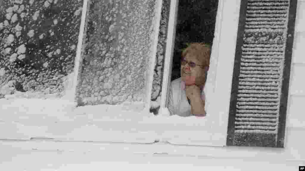 Rita Valente regarde, depuis la fenêtre, la neige tomber dans le quartier East Boston de Boston, dimanche 15 février, 2015. Une tempête a apporté un nouveau cycle de vent fouettée neige en Nouvelle-Angleterre, le dimanche.
