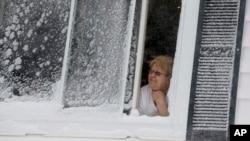 Seorang warga melongok dari jendelanya untuk melihat salju di East Boston, Boston (15/2). (AP/Michael Dwyer)