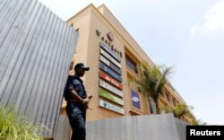A security guard stands outside the Westgate shopping mall that has been left deserted following last year's attack by al-Shabab gunmen in Nairobi that killed at least 67 people, Sept. 18, 2014.