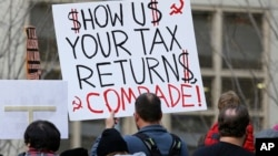 "Tax FILE - A protester in Seattle holds a sign during a rally that reads ""Show us your tax returns, Comrade"" in reference to calls for President Donald Trump to release his tax returns and his alleged ties to Russia, April 15, 2017."