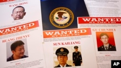 Wanted posters of Chinese military officers charged with cyber spying are on displayed May 19, 2014.