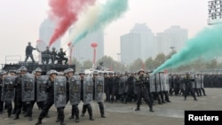 Policemen and members of the Special Weapons and Tactics practice dispersing crowds ahead of next week's 18th National Congress of the Communist Party of China, in Zhengzhou, Henan province, October 30, 2012.