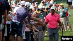 Tiger Woods of the U.S. slaps hands with patrons as he walks to the 8th tee during practice for the 2018 Masters golf tournament at Augusta National Golf Club in Augusta, Georgia, April 2, 2018.