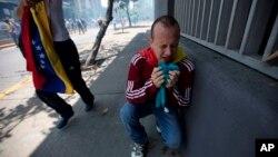 Un manifestante se arrodilla en el suelo abrumado por gases lacrimógenos despedidos por la Policía Nacional Bolivariana en Caracas, Venezuela, el sábado 8 de abril de 2017.