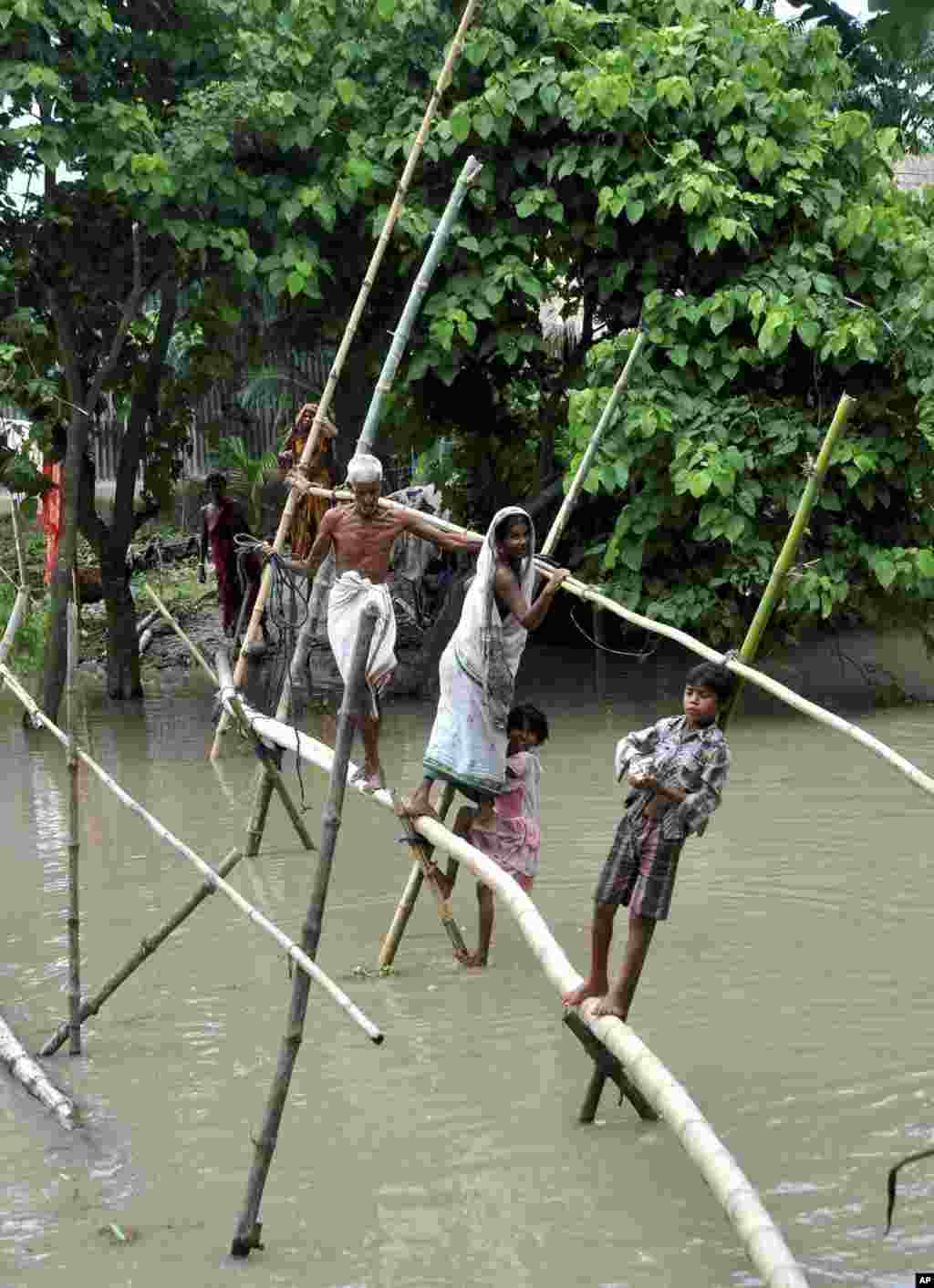 Indian villagers use a bamboo structure to move across a flooded village in the northeastern Assam state, India, Aug. 18, 2014.