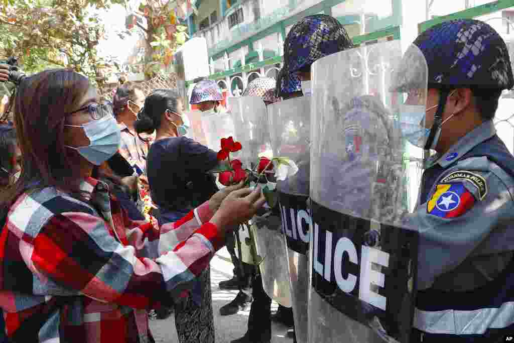 Supporters give roses to police while four arrested activists make a court appearance in Mandalay, Myanmar. Hundreds of students and teachers have taken to Myanmar's streets to demand the military hand power back to elected politicians.
