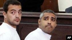 Phóng viên Mohamed Fahmy của hãng thông tấn Al-Jazeera (phải) và đồng nghiệp Baher Mohame tại phiên tòa ở Cairo.