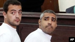 FILE - Al-Jazeera English producer Baher Mohamed, left, and Canadian-Egyptian acting Cairo bureau chief Mohammed Fahmy appear in court during their trial on terror charges, in Cairo, Egypt.