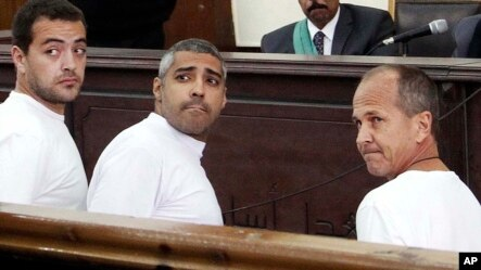 FILE - Al-Jazeera English producer Baher Mohamed, left, Canadian-Egyptian acting Cairo bureau chief Mohammed Fahmy, center, and correspondent Peter Greste, right, appear in court during their trial on terror charges, in Cairo, Egypt.