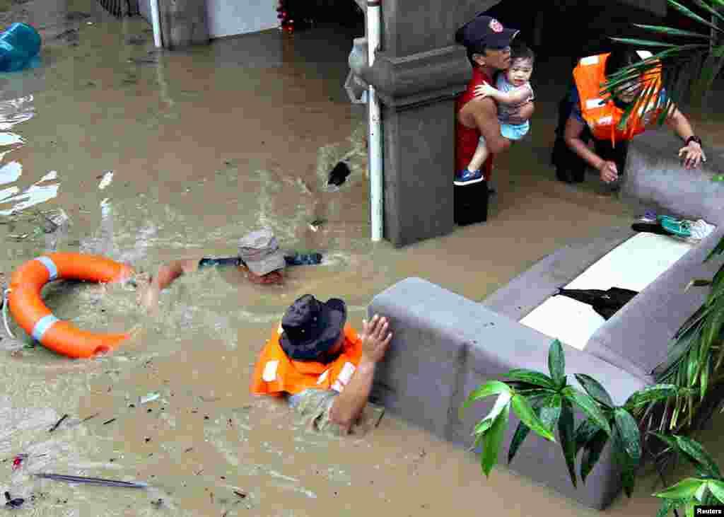 Cảnh sát sơ tán những gia đình bị mắc kẹt trong nhà của họ trong trận lụt lớn ở Misamis Oriental, đảo Mindanao ở miền nam Philippines, ngày 29 tháng 12, 2014.
