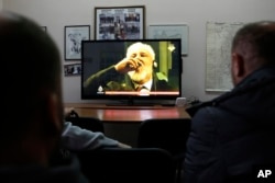 FILE - Bosnians watch a live TV broadcast from the International Criminal Court for the former Yugoslavia (ICTY) in The Hague as Slobodan Praljak drinks from a bottle that was later confirmed to have contained poison, in southern Bosnian town of Mostar 140 kms south of Sarajevo, Nov. 29, 2017.