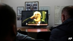 "Bosnian people watch the live TV broadcast from the International Criminal Court for the former Yugoslavia (ICTY) in The Hague as Slobodan Praljak brings a bottle to his lips, in southern Bosnian town of Mostar 140 kms south of Sarajevo, on Wednesday, Nov. 29, 2017. Praljak yelled, ""I am not a war criminal!"" and appeared to drink from a small bottle, seconds after judges reconfirmed his 20-year prison sentence for involvement in a campaign to drive Muslims out of a would-be Bosnian Croat ministate in Bosnia in the early 1990s."