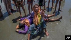 A Rohingya Muslim woman, who crossed over from Myanmar into Bangladesh, shouts for help as a relative lies unconscious after the boat they were traveling in capsized minutes before reaching shore at Shah Porir Dwip, Bangladesh, Thursday, Sept. 14, 2017. N