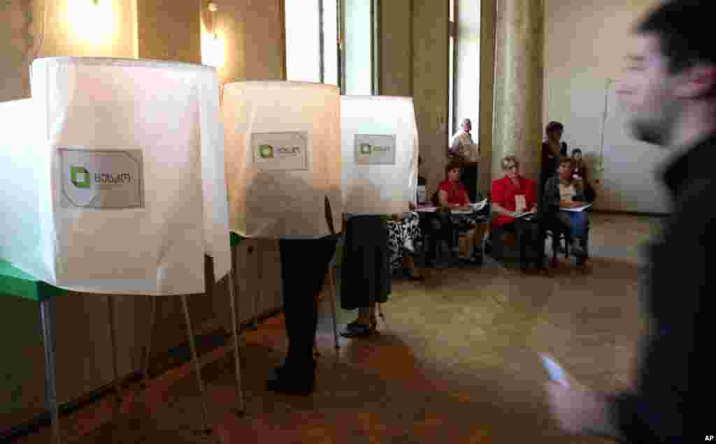 Georgians vote during Parliamentary elections at a polling station in Tbilisi, October 1, 2012. Voters in Georgia are choosing a new parliament in a heated election that will decide the future of Saakashvili's government.