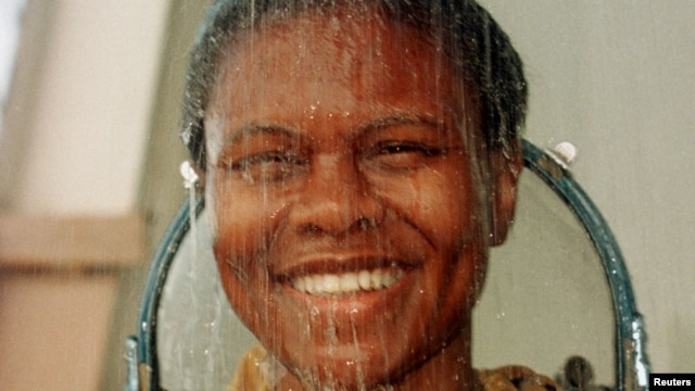U.S. astronaut Yvonne Cagle smiles as she takes a shower in her space suit after training in the Black Sea near Kudepsta, Russia, June 27, 1999. Cagle recently talked about her training at Town Hall Los Angeles, where she urged students to reach for the stars.