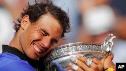 Petenis Spanyol Rafael Nadal memegang piala Perancis Terbuka setelah mengalahkan Stan Wawrinka dalam tiga set: 6-2, 6-3, 6-1 di Paris, Minggu (11/6).