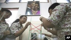 A portrait of U.S. President Barack Obama and his wife Michelle is seen hanging on the wall as students build a structure from straws during a class at an elementary school he once attended in Jakarta, Indonesia (Feb 2010 file photo)