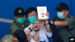Pro-democracy activist Avery Ng, center, holds a book with a cover picture of Chinese President Xi Jinping as he is escorted by Correctional Services officers to a prison van for a court in Hong Kong, May 28, 2021.