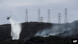 A helicopter drops water near power lines and electrical towers while working at a fire on San Bruno Mountain near Brisbane, California, Oct. 10, 2019.
