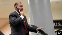 Sen. Lindsey Graham, R-S.C., talks on the phone as he rides the escalator on Capitol Hill in Washington, July 10, 2019, as he heads to a briefing on election security.