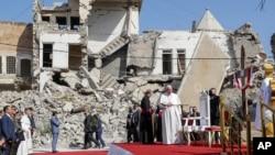 Paus Fransiskus, yang dikelilingi oleh puing-puing gereja yang hancur, tiba untuk berdoa bagi para korban perang di Lapangan Gereja Hosh al-Bieaa, di Mosul, Irak, yang pernah menjadi ibu kota de-facto ISIS, Minggu, 7 Maret 2021. (Foto: AP)