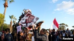 Supporters of the Libyan National Army hold a picture of Turkish President Recep Tayyip Erdogan as they celebrate near a Turkish military armored vehicle, which the LNA said it confiscated during Tripoli clashes, in Benghazi, Jan. 28, 2020.