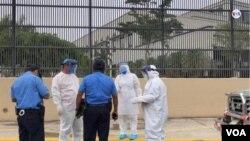 La policía y personal de salud recoge a una persona que se desplomó en el piso, en medio de la pandemia de coronavirus en Nicaragua. [Foto: Daliana Ocaña/VOA]