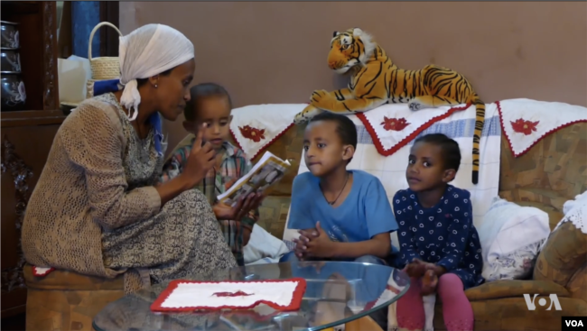 Meaza Takele reads the 'Tibeb Girls' comis strip to her young children.