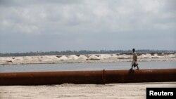 Un homme se promène près d'un oléoduc aux alentours des plages de Akodo, Lagos, le 25 juin 2016.
